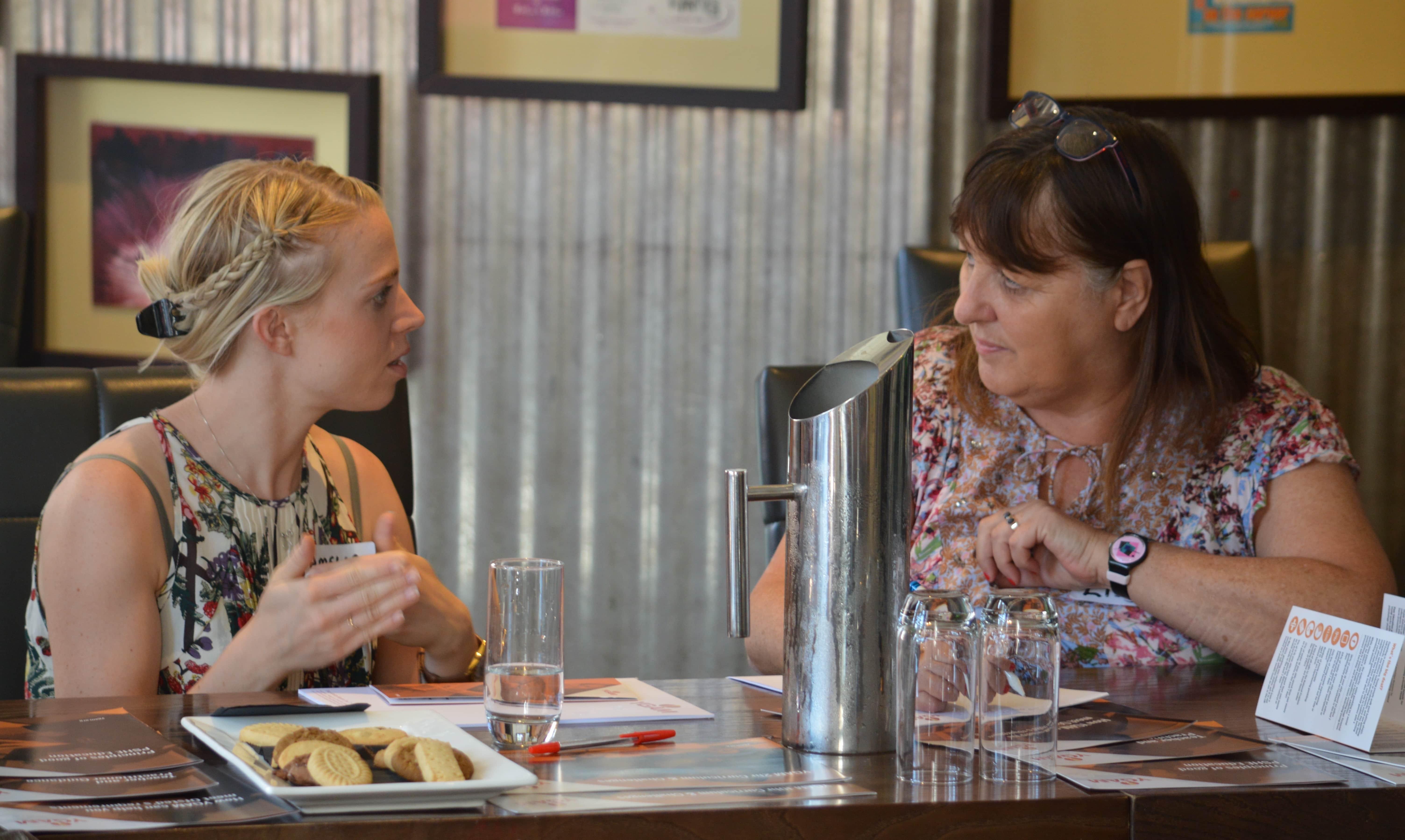 Two women talking at YGAM workshop