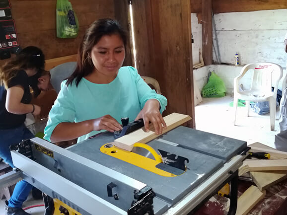 Photo of a Guatemalan girl learning to use a table saw