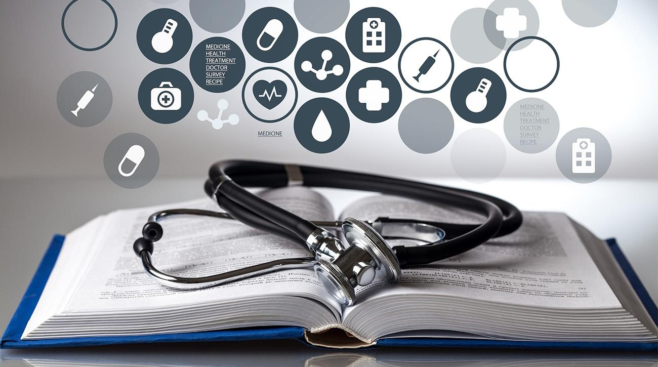 health symbols with stethoscope on top of book