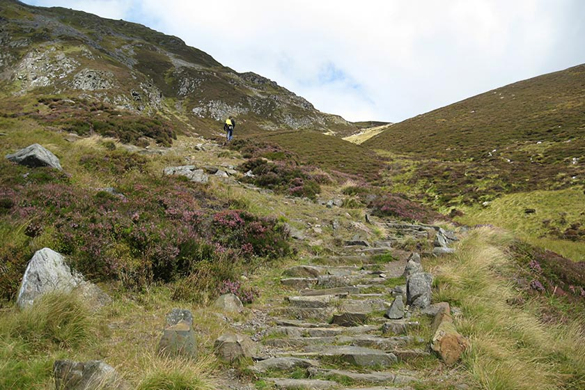 Photo of steps that form part of a walking path up a Munro. There is a lone walker on the path in the distance