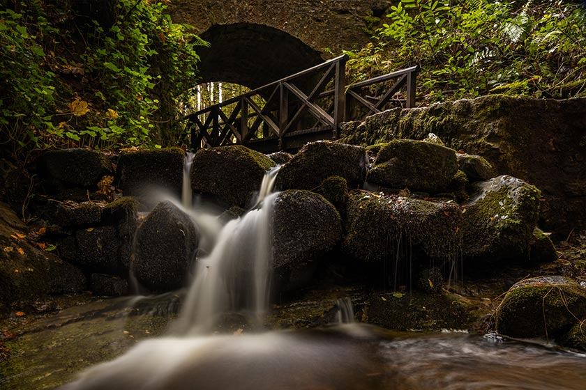 Photo of a stream flowing over rocks with an arched bridge in the background