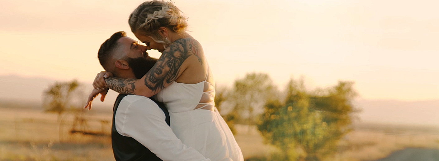 Groom holding bride in a field in Chico, Ca