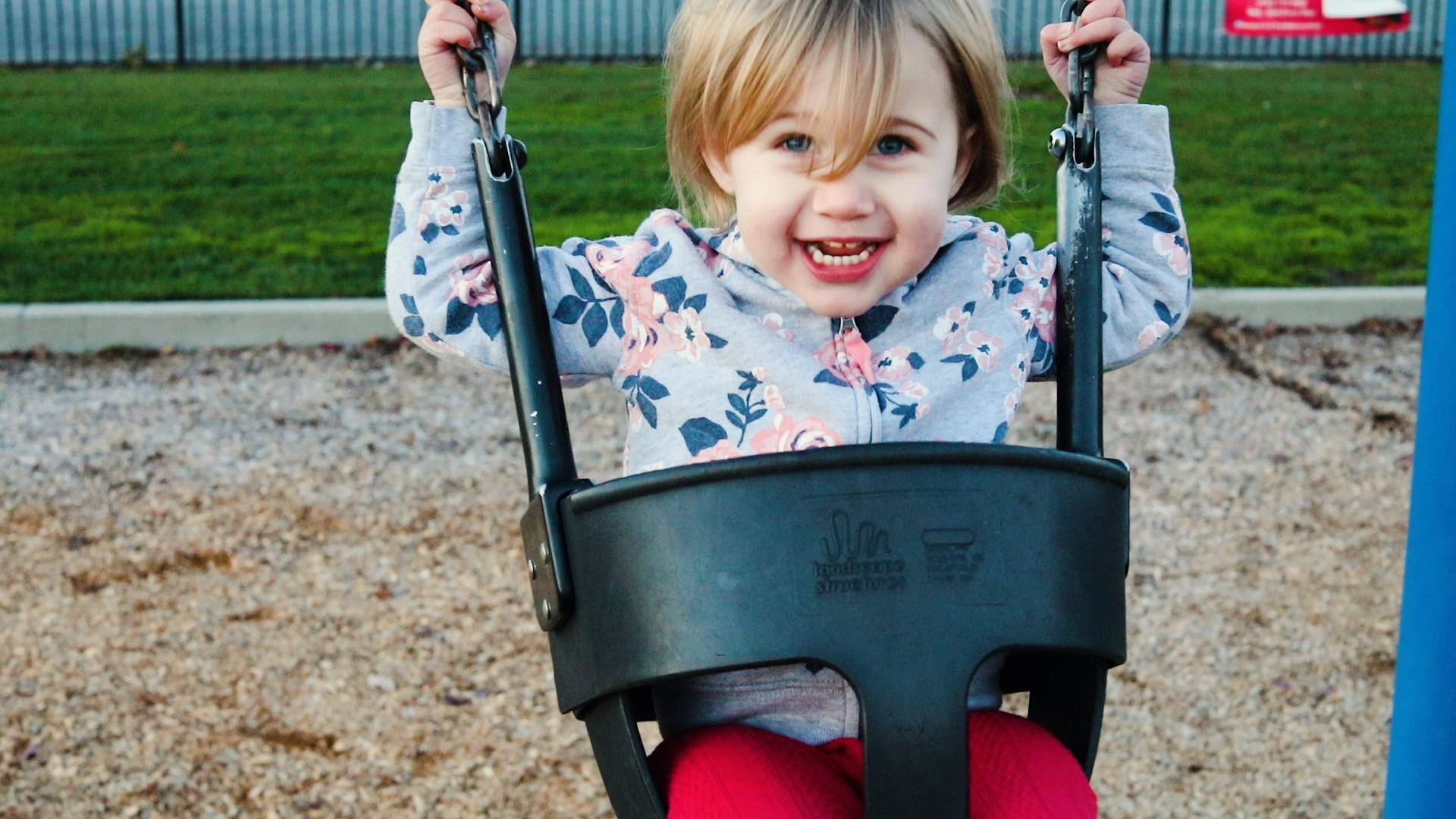 Young Girl smiling while swinging on a swing in the park