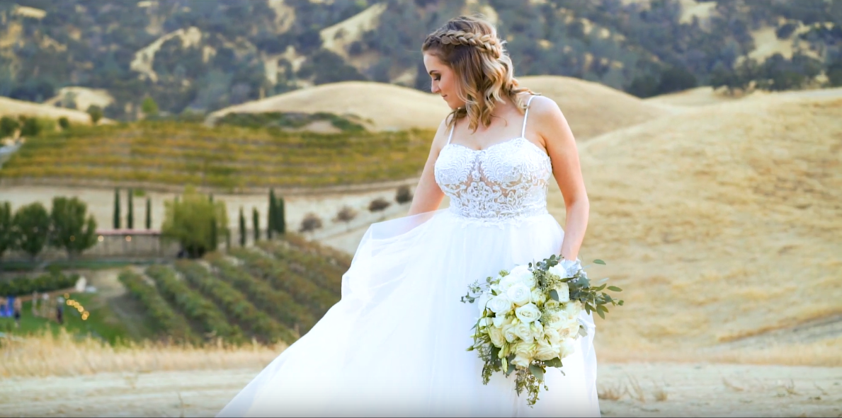 a Bride Displaying her dress in the golden fields of her wedding venue at Taber Ranch