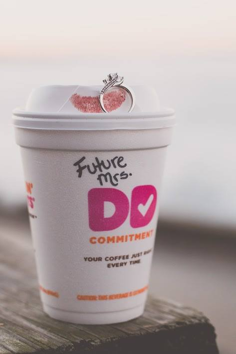 Engagement photo featuring a Dunkin Donuts cup with an engagement ring on top.