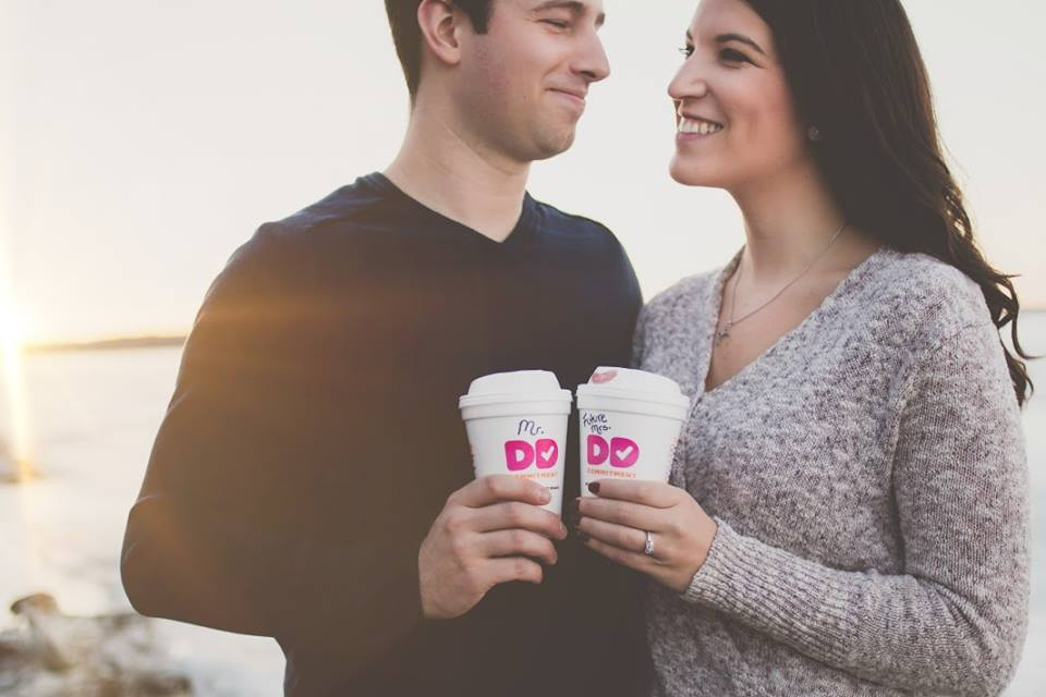 Engagement photos featuring an obsessed Dunkin Donuts brand fan with her fiance and two Dunkin Donuts cups in their hands.