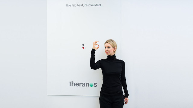 A picture of Elizabeth Holmes holding a tiny vile of blood standing in front of a Theranos poster.