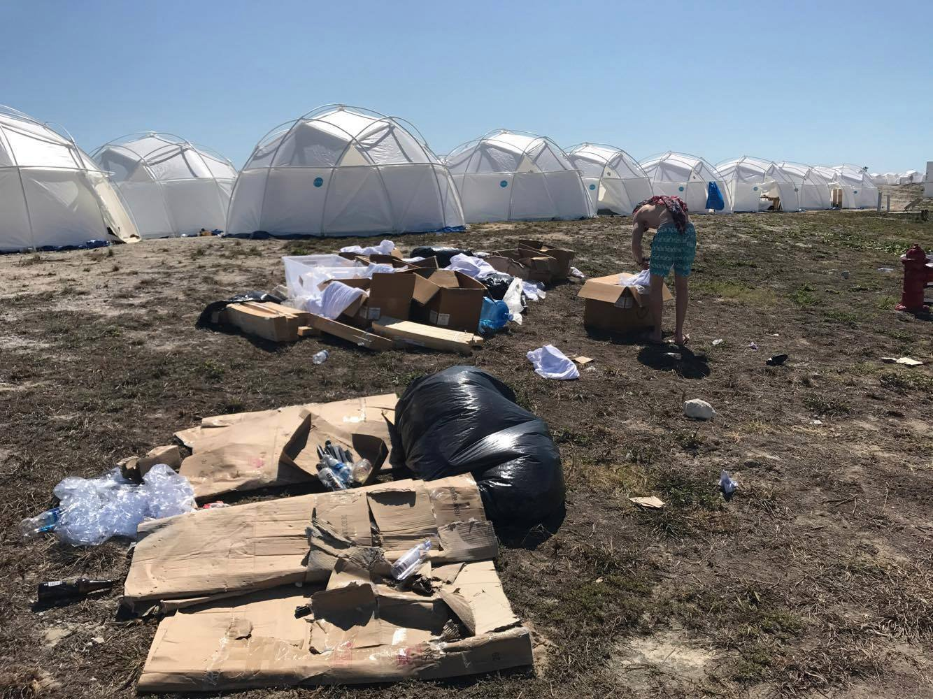 Fyre festival grounds. Cheap tents are set up with trash everywhere.