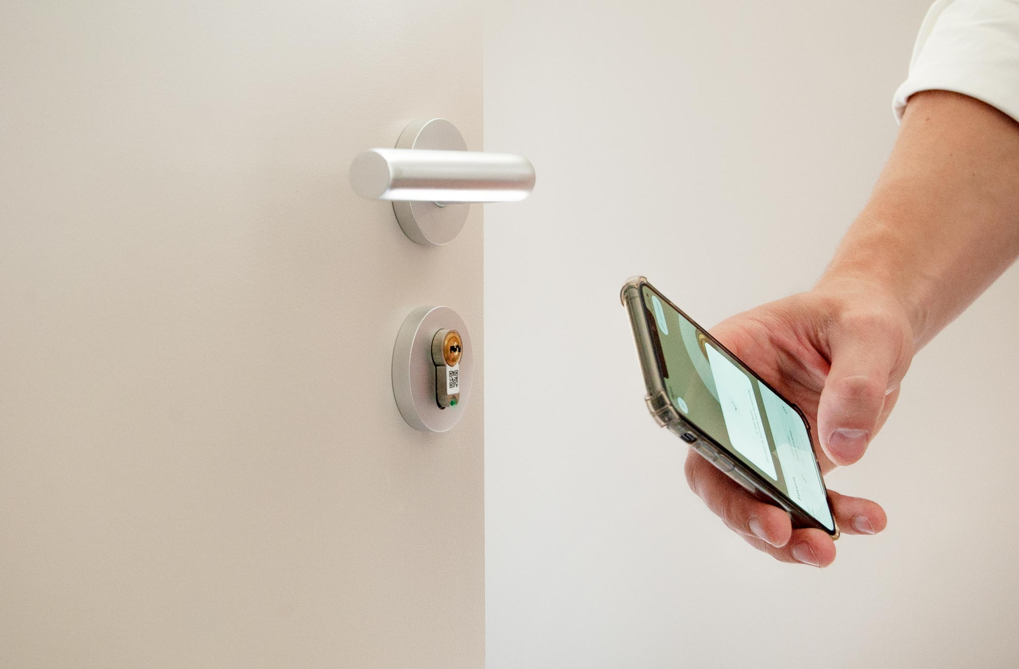 A user using their mobile phone to flash the BrightLock installed on a door.