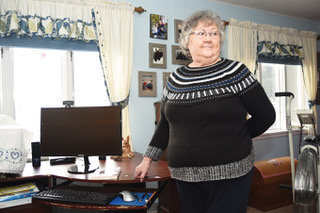 """Longtime resident Bonita Hunt stands in her bedroom next to the computer she used to digitize the typewritten manuscript of her first novel, """"Warbo,"""" which she first began writing in the 1960s."""