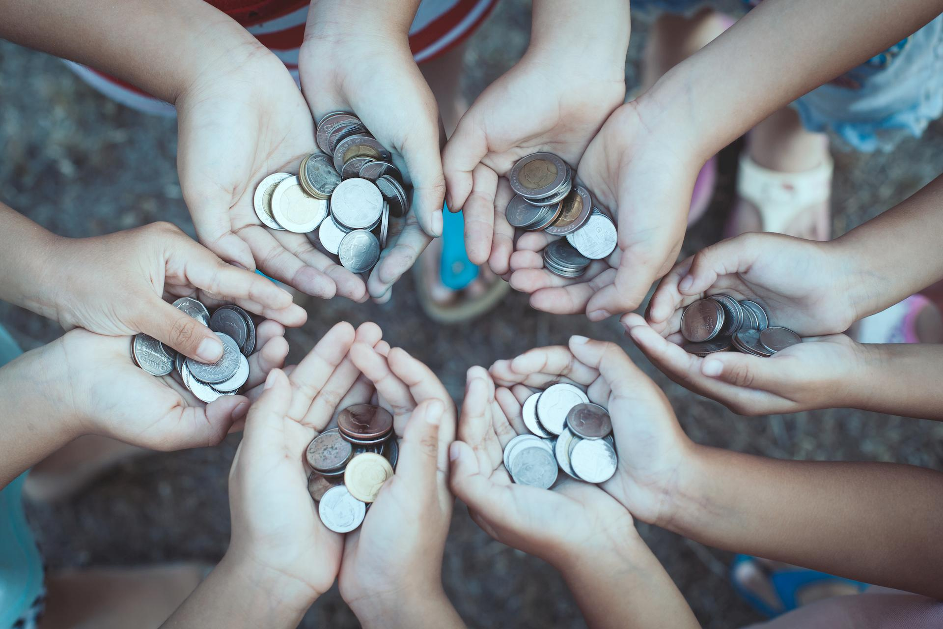 Group of people holding coins in hands