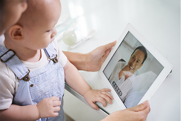 Image of parent holding baby looking at iPad.