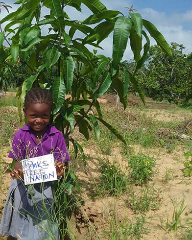 Girl in Africa holding up thank you sign