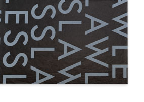 """A sheet of black tissue paper with the word """"Flawless"""" printed in large white letters"""