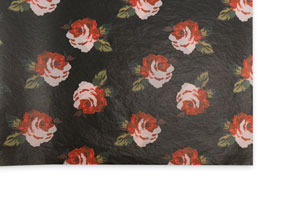 A sheet of printed tissue paper with bright flowers on a black background