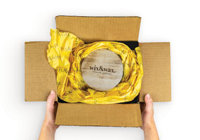 hands unboxing an eCommerce package with custom printed yellow packaging paper
