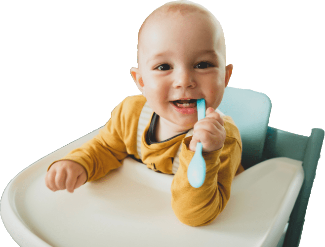smiling baby in high chair waiting for food