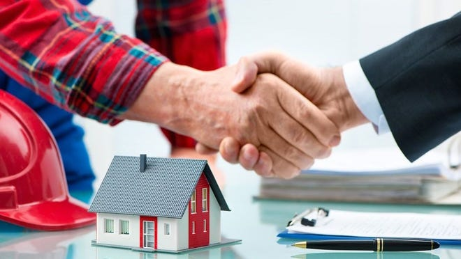 Two hands shaking over a table with a model house, pen, and documents.