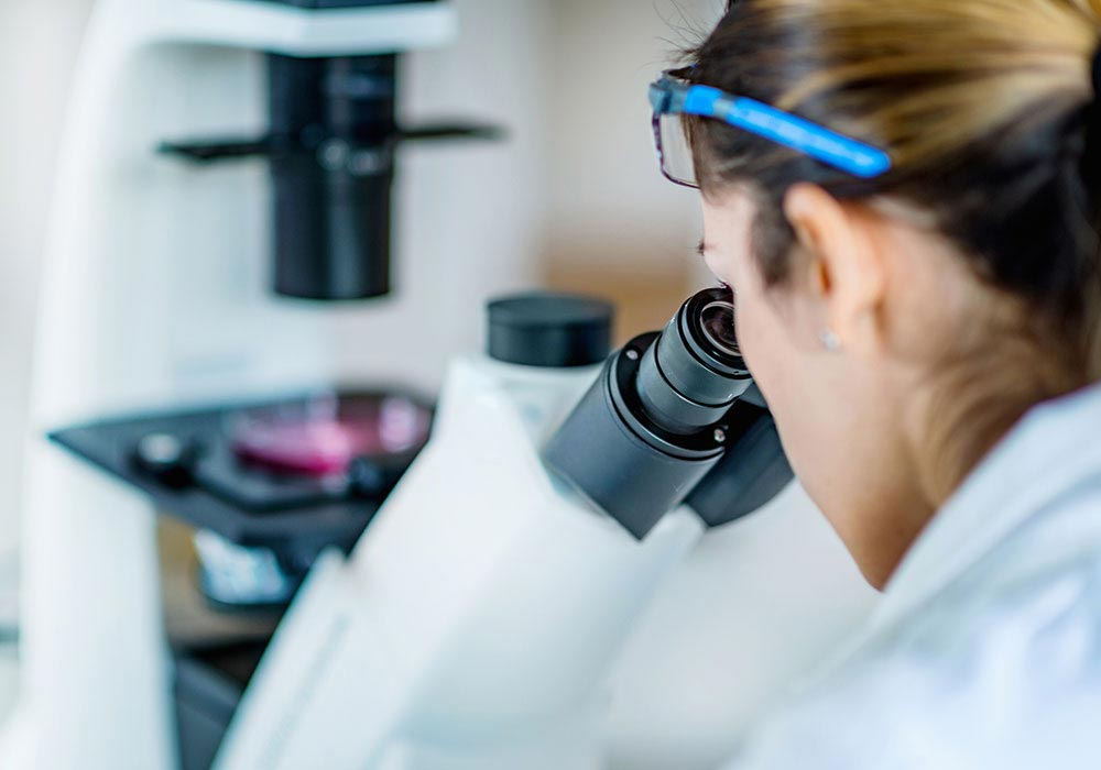 woman in lab looking into microscope to gather data for clinical research study