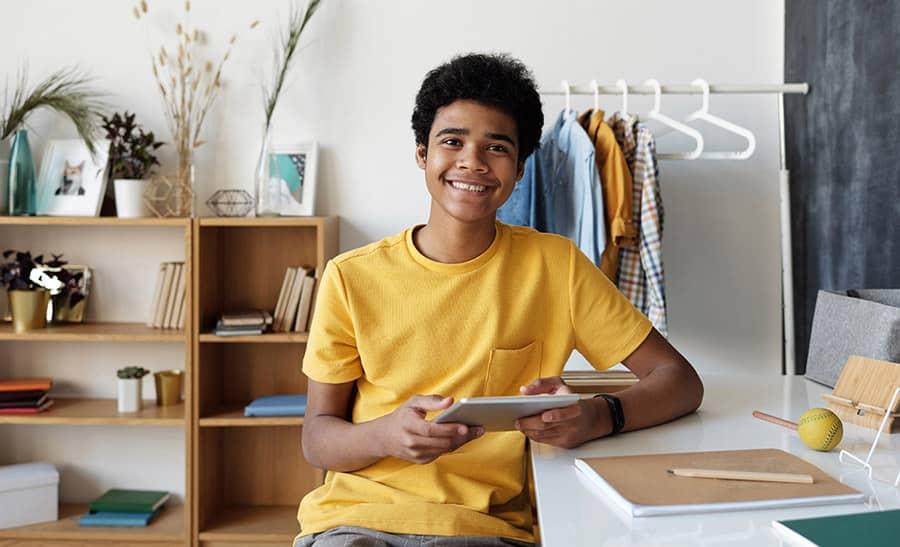 Teen boy in yellow shirt smiling