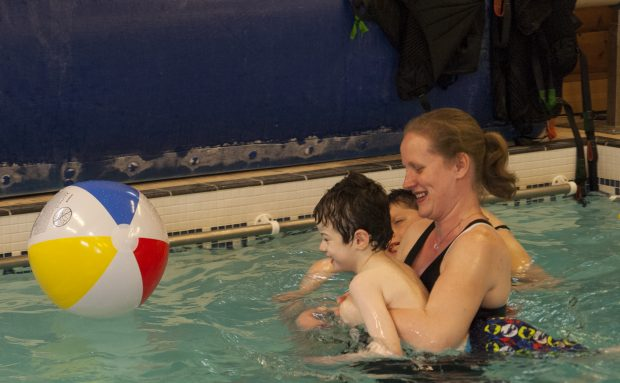 Little boy in the pool with their teacher with the teacher supporting the boy to play with a floating ball.