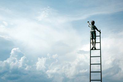 boy on ladder reaching for sky
