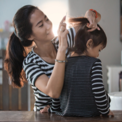 Image of mother doing child's hair