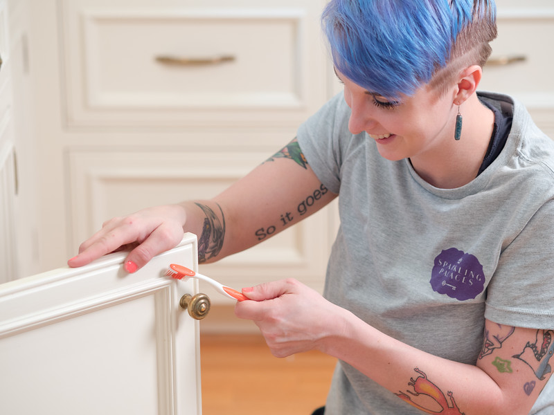 Woman cleaning a white cabinet with a toothbrush