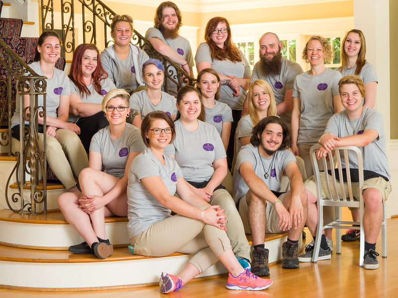Staff group picture smiling sitting on stairs