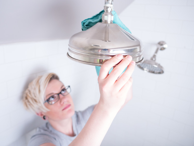 Woman cleaning a chrome showerhead