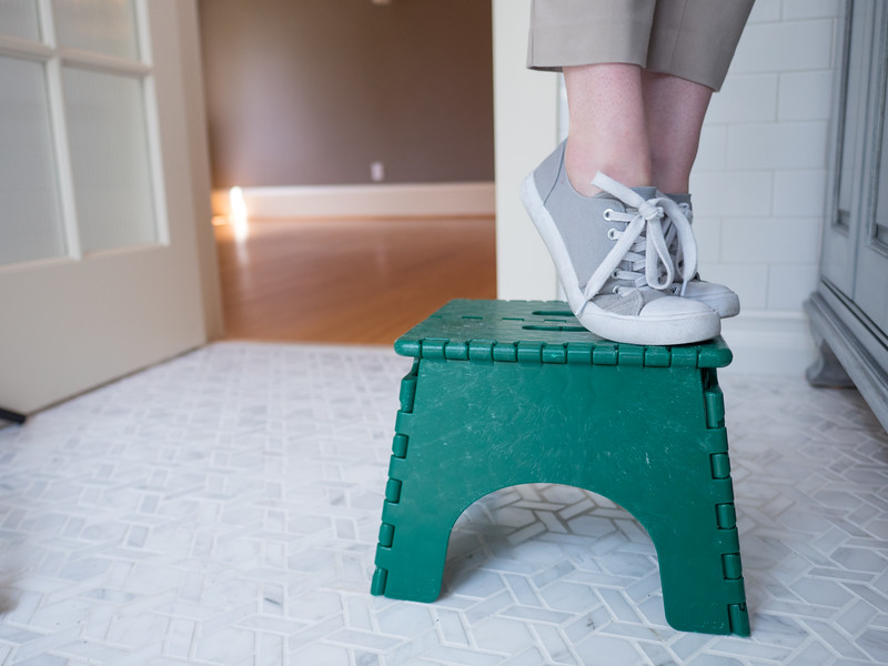 Amy standing on a small green stepstool