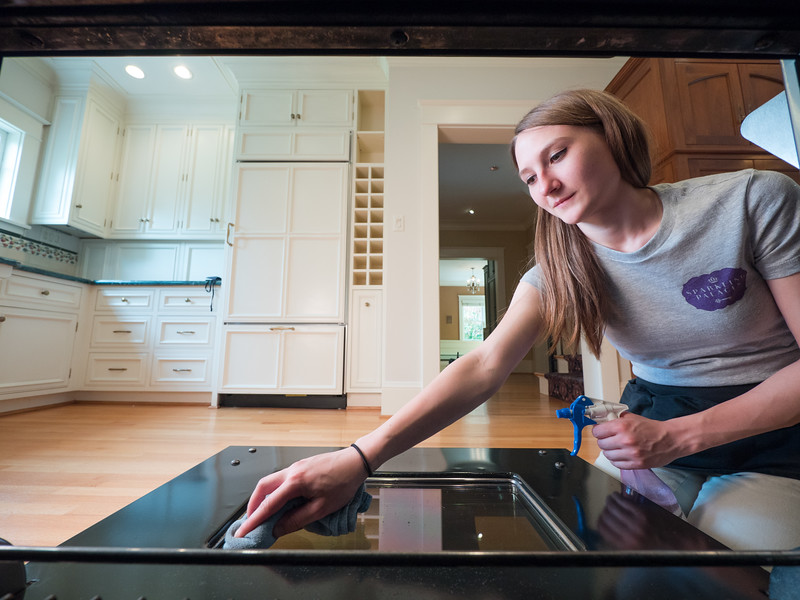 Woman deep cleaning the inside of an oven