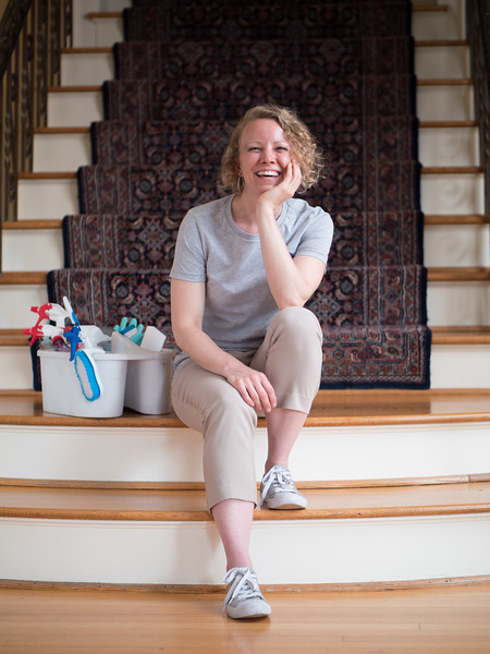 Owner Amy Boggs sitting on stairs next to cleaning supplies