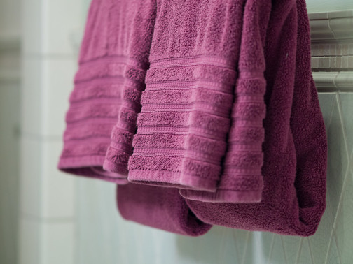 Two red towels folded and hanging in bathroom