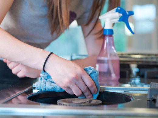 Woman deep cleaning a kitchen stovetop