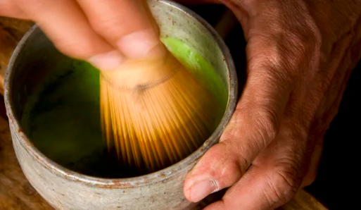 Green tea being prepared with a traditional whisk and bowl.