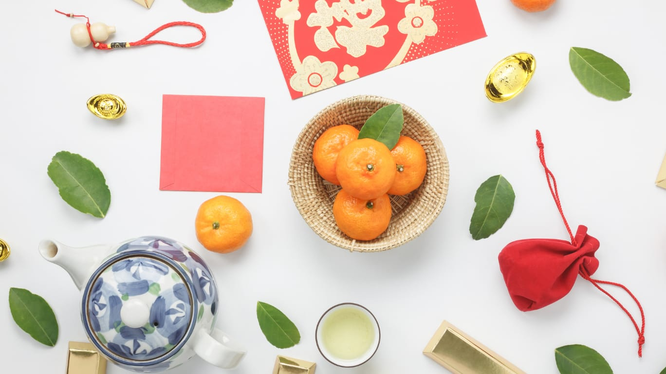 An assortment of items associated with Chinese new year, including a bowl of oranges, red envelopes, tea and gold.