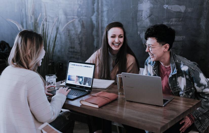 Parta studentek pracující na počítači v kavárně