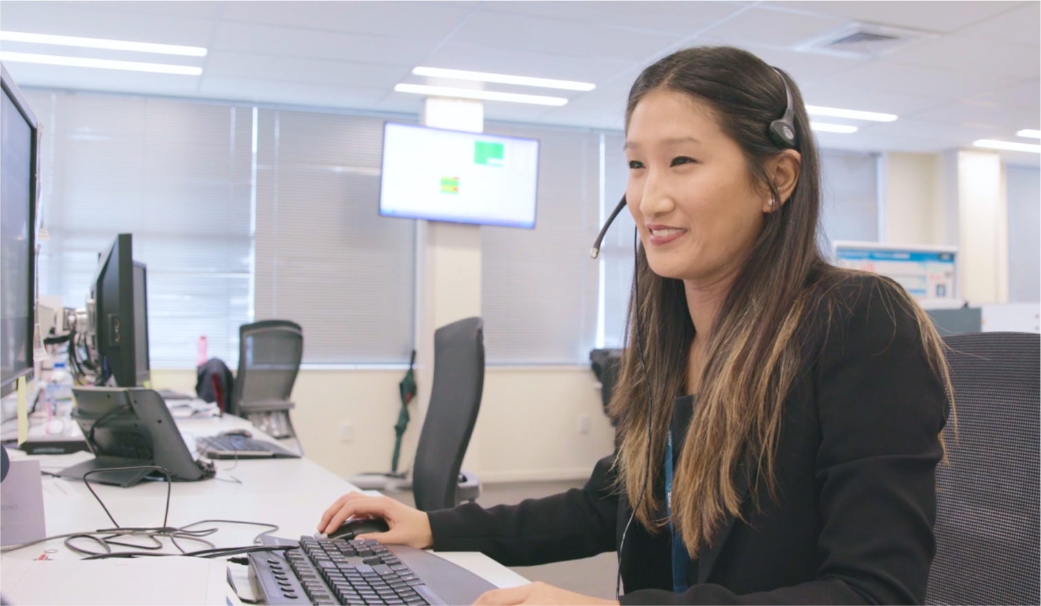 Female bank support staff member working at her computer talking a call