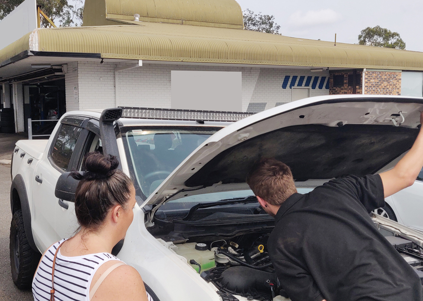 Mechanic examining a car engine as a woman looks on
