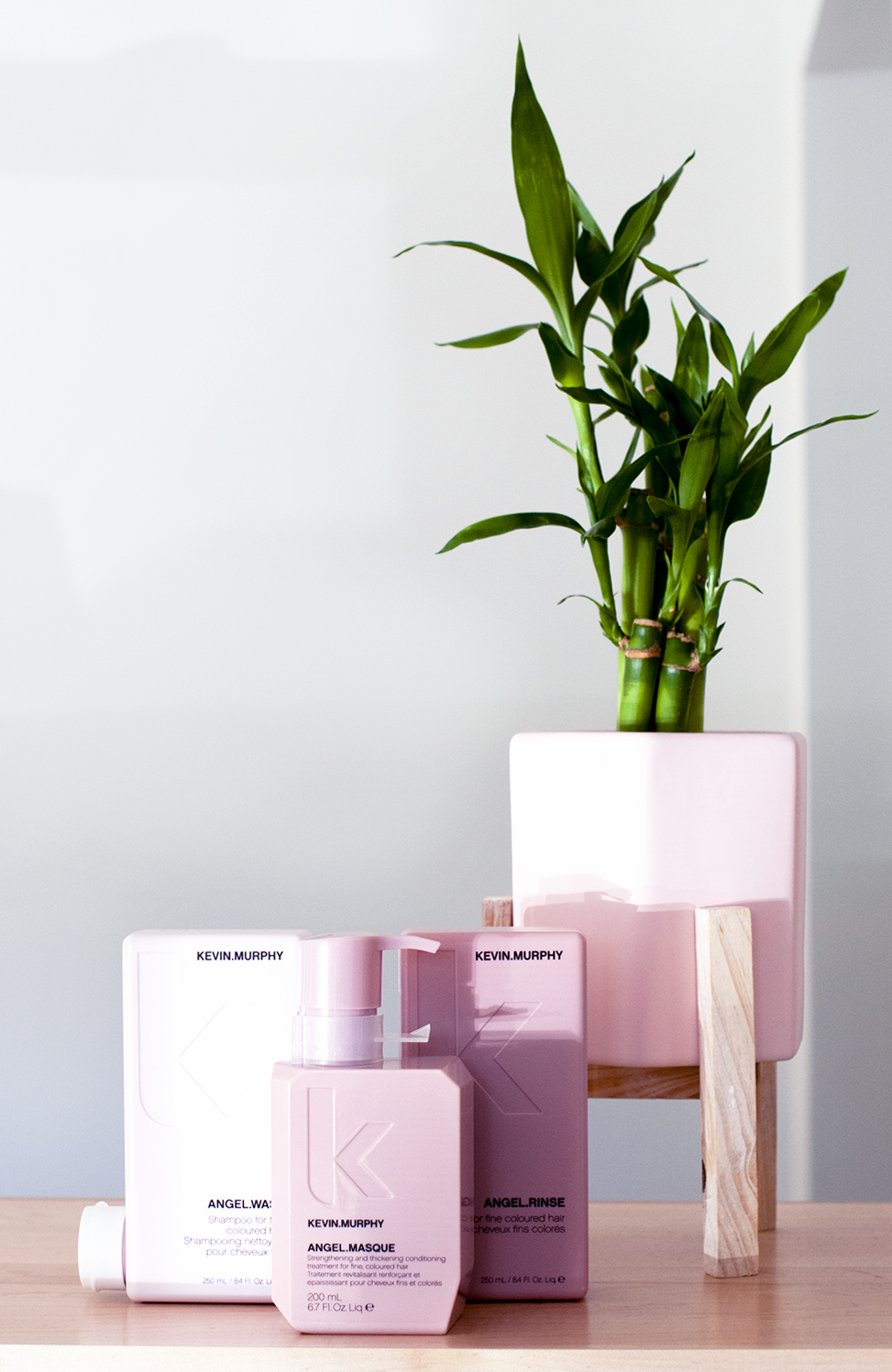 An assortment of pink KEvin Murphy products next to a green plant.