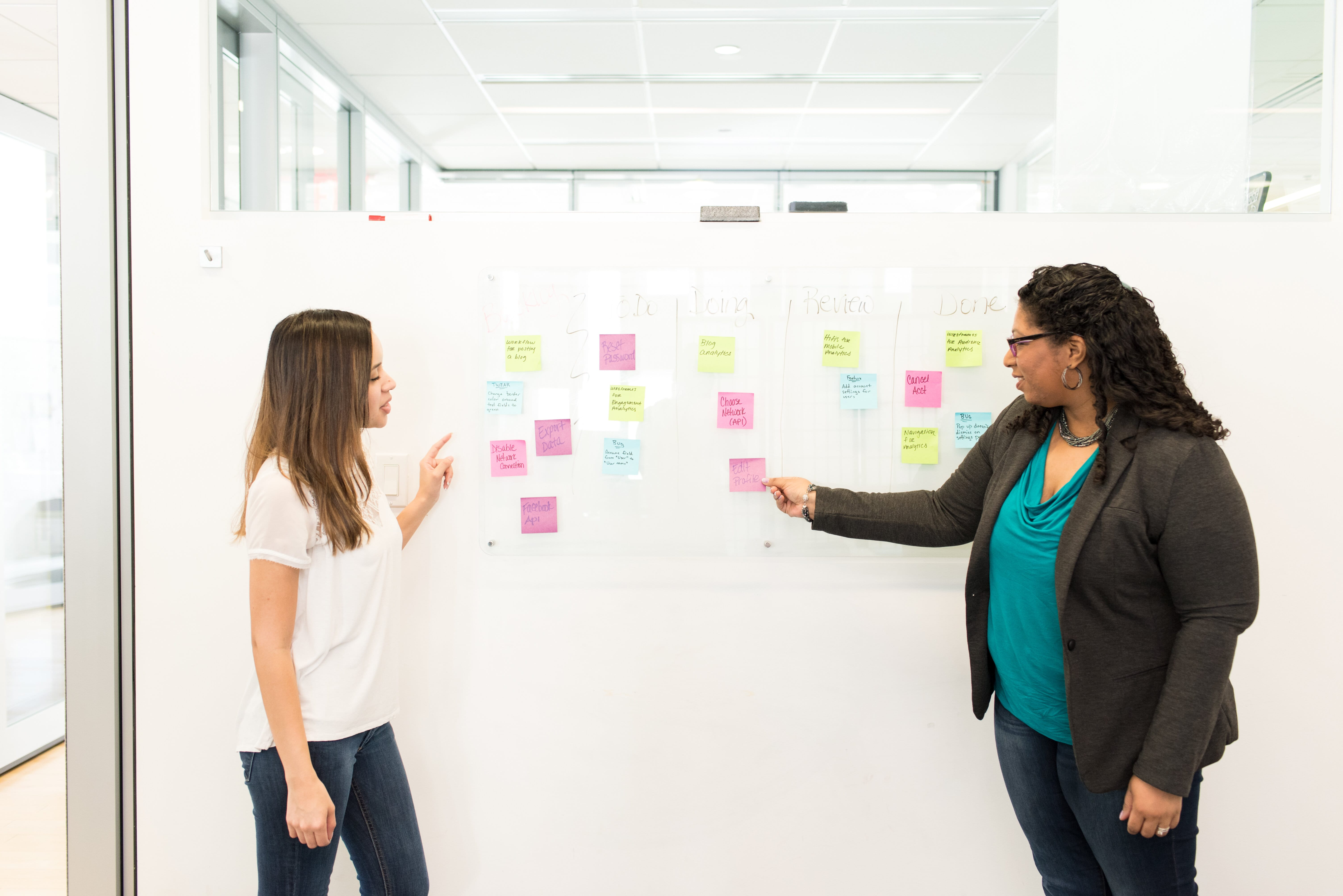 Two women standing at a white board with sticky notes completing the design thinking process
