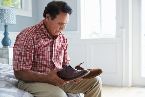 older man sitting on a bed holding 2 different shoes - he looks confused
