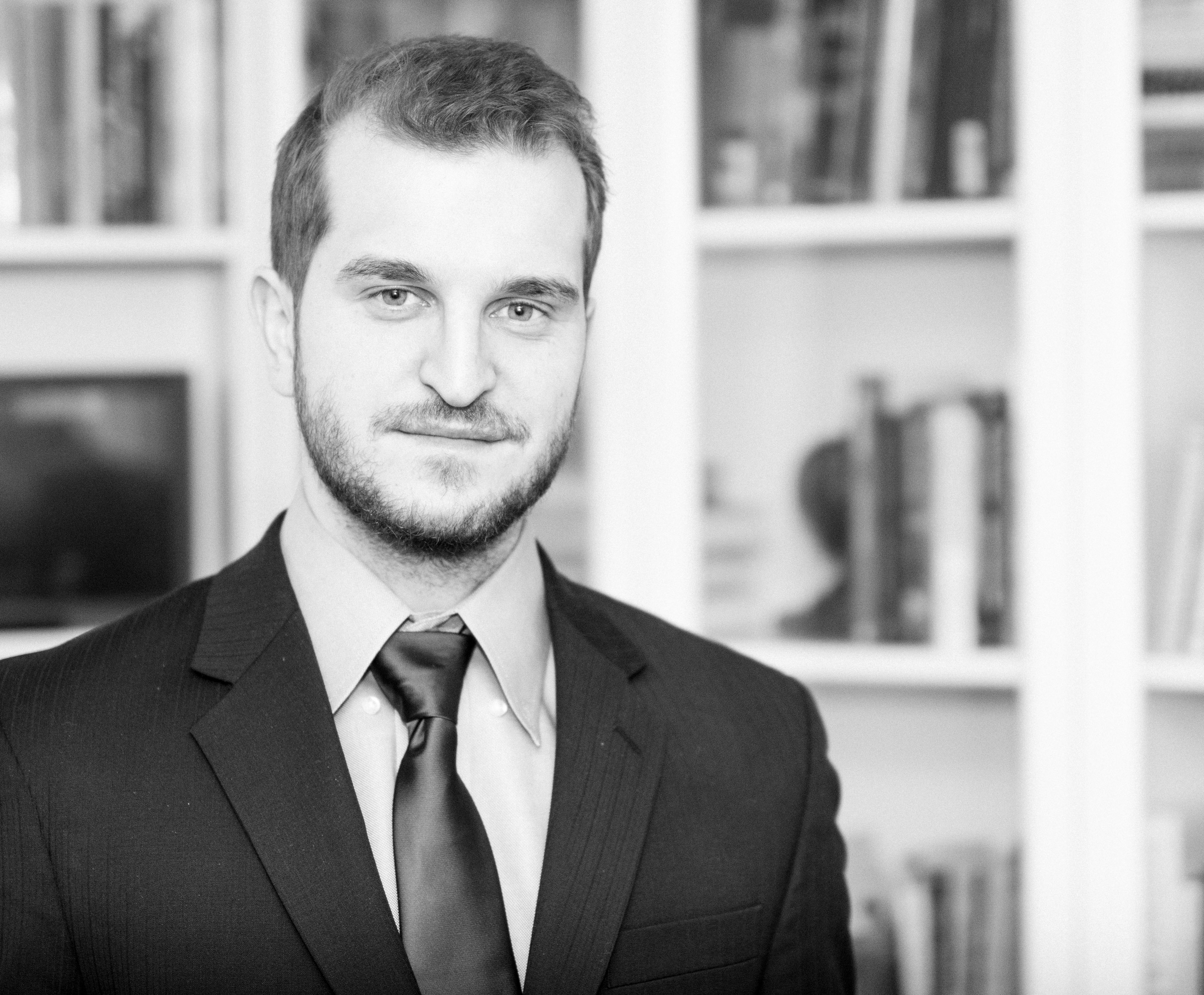 Bradley Machov Wearing a Suit Standing in front of a bookcase