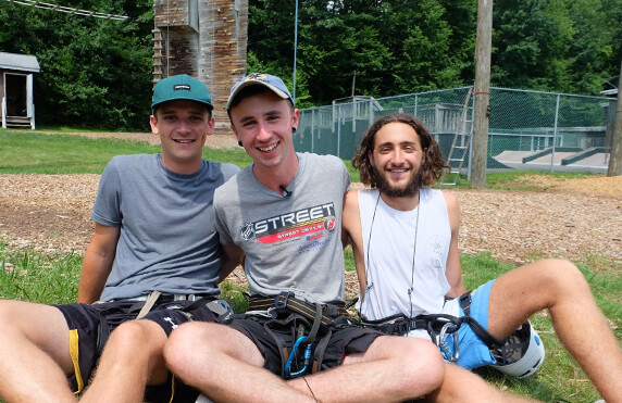 three male camp america counsellors smiling sitting on the grass