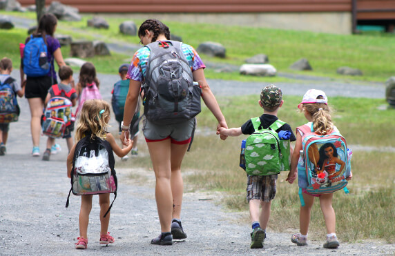 camp america counsellor walking alongside three young campers at a faith based camp