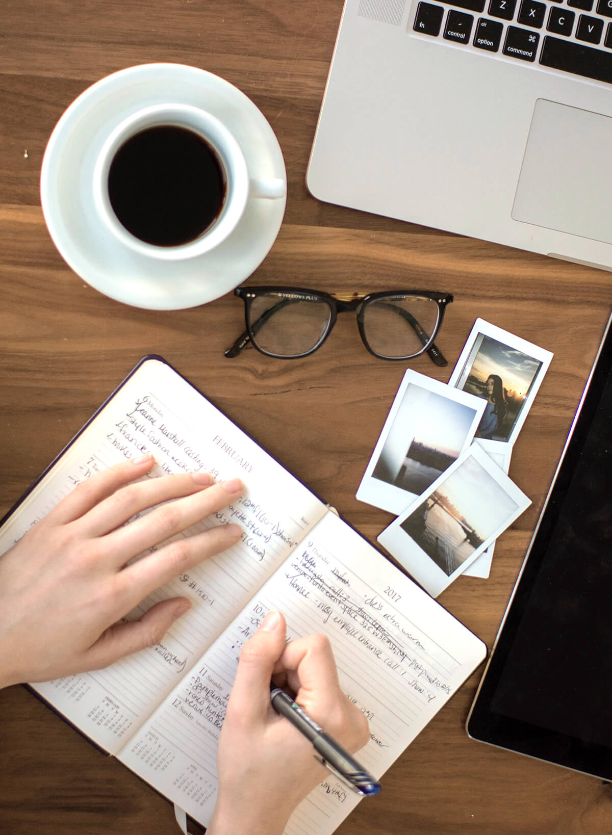 birdseye view of a person writing at a desk surrounded by coffee, photos, glasses and a laptop