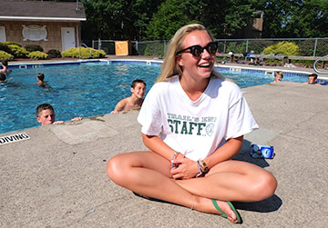 young female camp america counsellor sitting by the pool