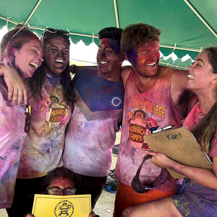 group of camp america counsellors laughing covered in coloured (holi) powder