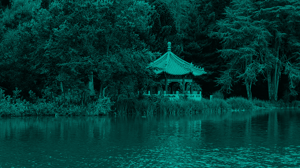 A pagoda sits at the edge of Stow Lake, surrounded by trees. There are tall grasses at the water's edge that obsure the bottom of the pagoda.